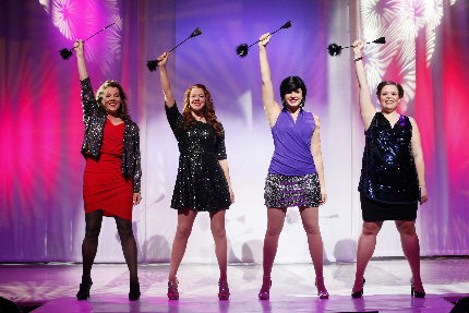 The cast of The D*Word raise a sex toy in triumph at the finale.