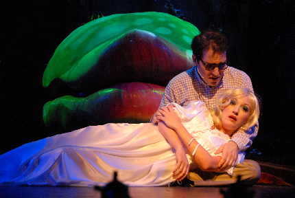Mike westrich as seymour comofrts Amy Miller Brennan as Audrey in front of the human-eating Audrey II (Rick Pena is probably inside) in Slow Burn theatre Company's Little Shop of Horrors / Photo by Gemma Bramham